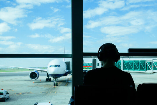 Rear View Of Man Looking Through Airplane Window