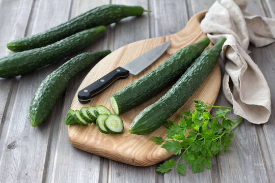 Long Chinese cucumbers on a cutting board while slicing salad. wood background. selective focus