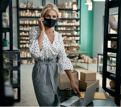 Female business owner in protective face mask talking by phone and using laptop while standing in her art studio or craft pottery shop with handmade ceramic products