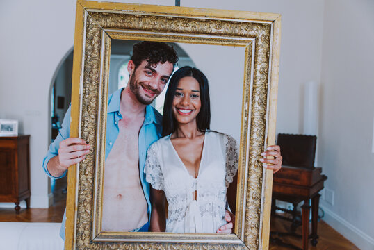 Portrait Of Smiling Young Couple Holding Picture Frame At Home