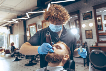 Close up man getting hair cut at the barbershop wearing mask during coronavirus pandemic. Professional barber wearing gloves. Covid-19, beauty, selfcare, style, healthcare and medicine concept.