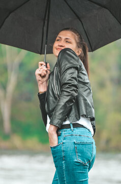 Woman Holding Umbrella While Standing On Rainy Day
