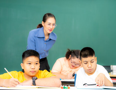 Asian kids with disability in special school classroom with Autism child and attrative teacher