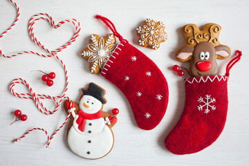 Christmas background postcard, red socks for gifts with gingerbread, gingerbread snowman, deer, snowflakes and red and white rope.