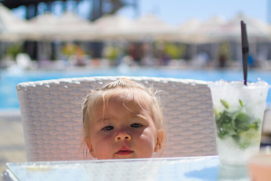 Caucasian girl portrait drinks mochito next to pool close up