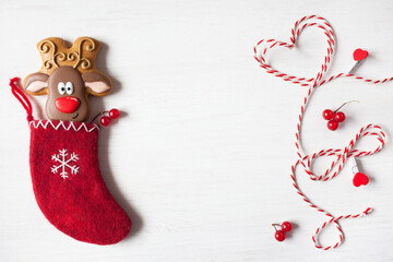 Christmas background postcard, red sock for a gift with gingerbread deer red and white rope on a white wooden table. space for congratulations text.
