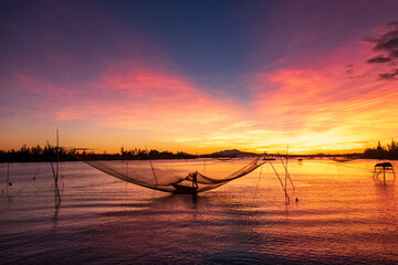 Silhouette of a fisherman checking his nets at sunrise, Vietnam