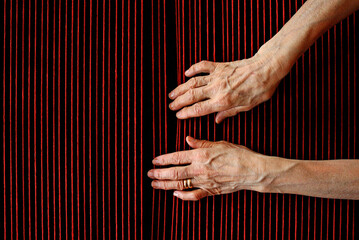 Elderly woman's hands touching red wool threads