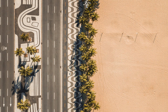 Aerial Top Down View Of Palm Trees On Empty Copacabana Beach, Alongside Famous Mosaic Sidewalk And Avenida Atlantica Road, During Coronavirus Lockdown In Rio De Janeiro, Brazil