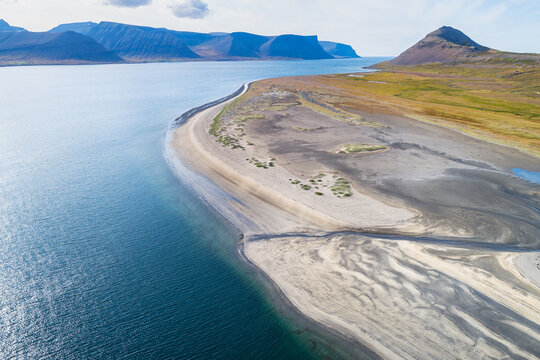 Aerial view of a stream through a beach in front of grassland and a mountain in a fjord, Dyrafjordur, Westfjords, Iceland