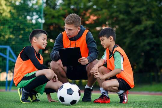 Professional soccer coach tells the strategy of football game to his attentive teen players at stadium during training.