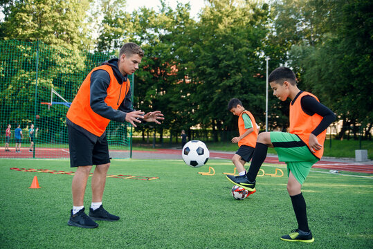 Young soccer coach instructs teen players. A young professional coach trains the ball kicks with young football players.