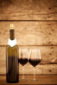 Two glasses of wine and a bottle on a wooden table.