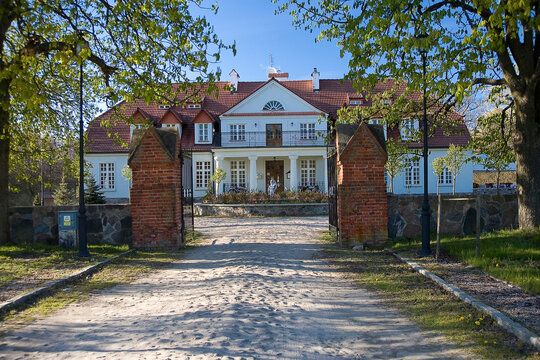white large mansion in Poland on a warm summer day with an entrance gate
