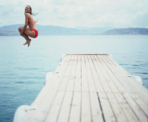 Woman jumping off the end of jetty into the sea.