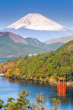 Japan, Central Honshu (Chubu), Fuji-Hakone-Izu National Park, Hakone, Mount Fuji (3776m) snow capped and viewed across lake Ashino-ko with the red torii gates of Hakone-jinja rising from the lake