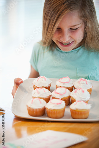 Mother's Day: Girl Happy with Work on Mom's Cupcakes