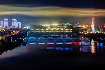 Democratic People's Republic of Korea (DPRK), North Korea, Pyongyang, new modern buildings in the centre of Pyongyang colourfully illuminated at night Fotomurales
