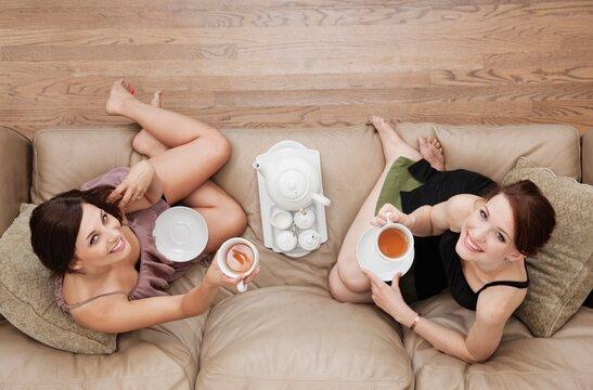 Portrait of two young women enjoying tea on sofa