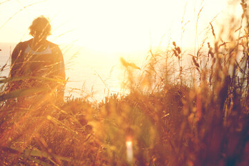 Young man daydreaming while walking through high grass in warm sunlight