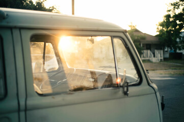 White vintage bus with sun flare in window