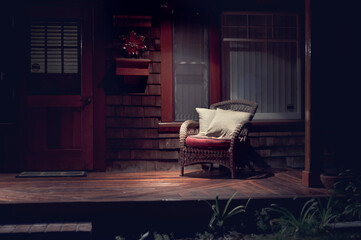 A cozy chair on a dark wooden deck at night