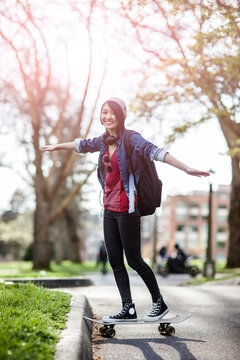 Asian college student riding her skateboard on campus