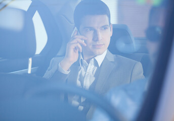 Businessman sitting in a backseat of the car and talking on the phone.