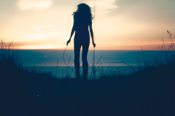 a woman on the edge at sunset