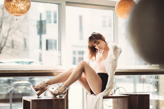 A beautiful model sitting by a counter at a lounge pushing back her hair