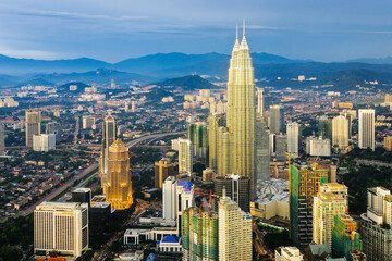 Asia, Malaysia, Selangor State, Kuala Lumpur, elevated view of iconic 88 storey steel-clad Petronas Towers and KL city centre skyline - illuminated at dusk