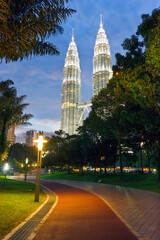 Asia, Malaysia, Selangor State, Kuala Lumpur, KLCC - Kuala Lumpur City Centre - urban development which includes the KLCC park, convention and shopping centre and the iconic 88 storey steel-clad Petronas Towers - illuminated at dusk