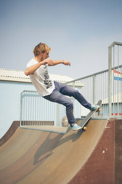 Young man balancing on a rail with his skateboard