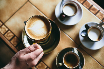 A hand lifts a cup of cappuccino.