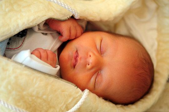 Madagascar, Antananarivo, one week old mixed race baby sleeping