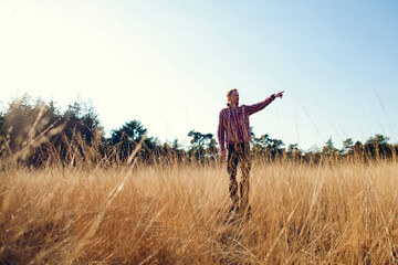 Man standing in high grass pointing at something