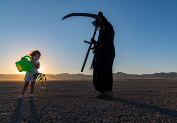 horror grim reaper holding is holding a clock in one hand and a scythe in the other. A green plant on the cracked ground and a little boy watering it. global climate change concept