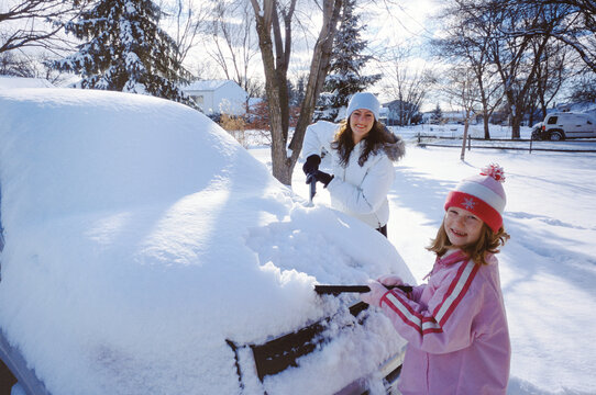 Mother and Daughter clearing snow from vehicle.