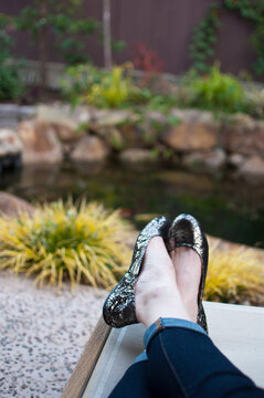 woman lounging near pond in garden