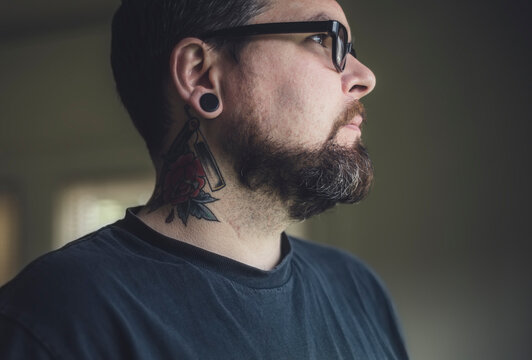 A handsome tattoo'd man in window light