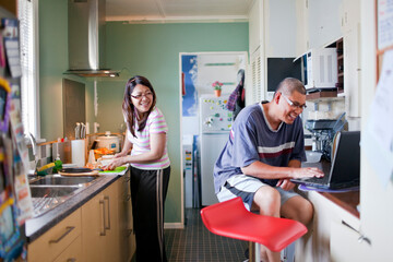 Husband Using Laptop and Wife Cooking in Kitchen Together