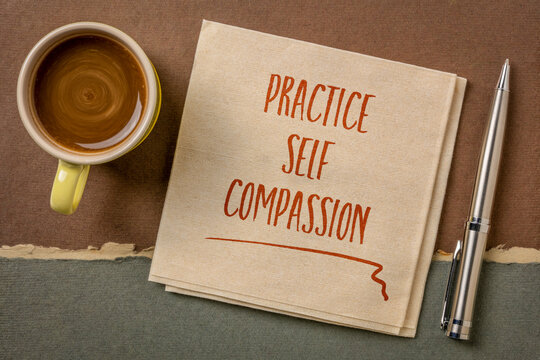 practice self-compassion inspirational handwriting on a napkin with coffee, mindset and personal development concept
