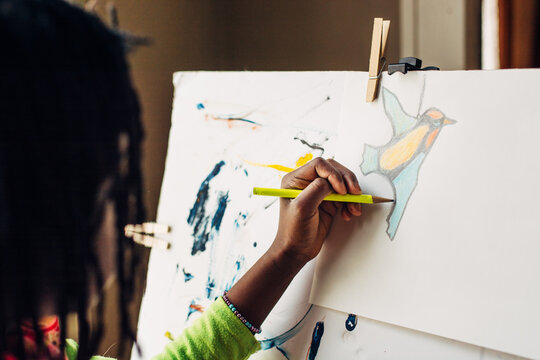 African American girl drawing a colorful bird