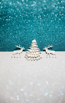 Festive scene with two deers and a pine tree on star shaped glitter blurry background