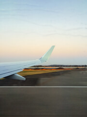 View of an airplane wing and rain on the window and tarmac