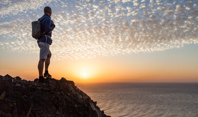 Hiker on mountain top looking at the sea on sunset