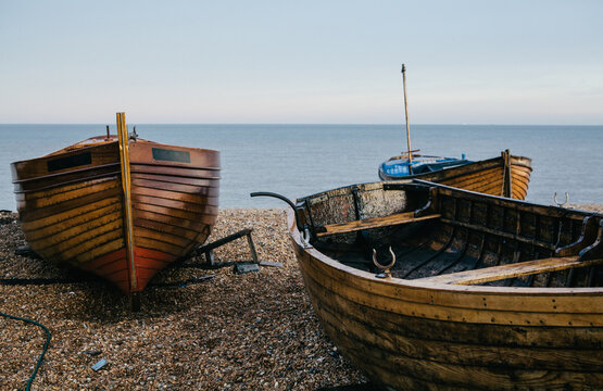 Traditional small wooden fishing boat on the shore.