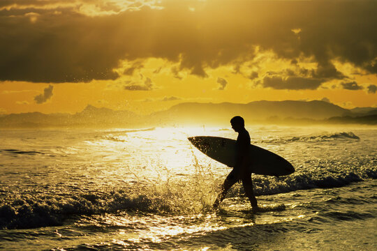 Young man surfing wave at sunset in Byron Bay Australia
