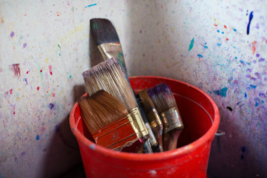 Many paint brushed in a red bucket inside a paint splattered sink