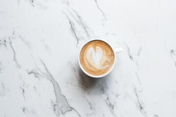 flat white coffee with a loveheart shape, on a marble background